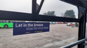 Photo of a sign on a bus reading 'Let in the breezer, blow the virus away'